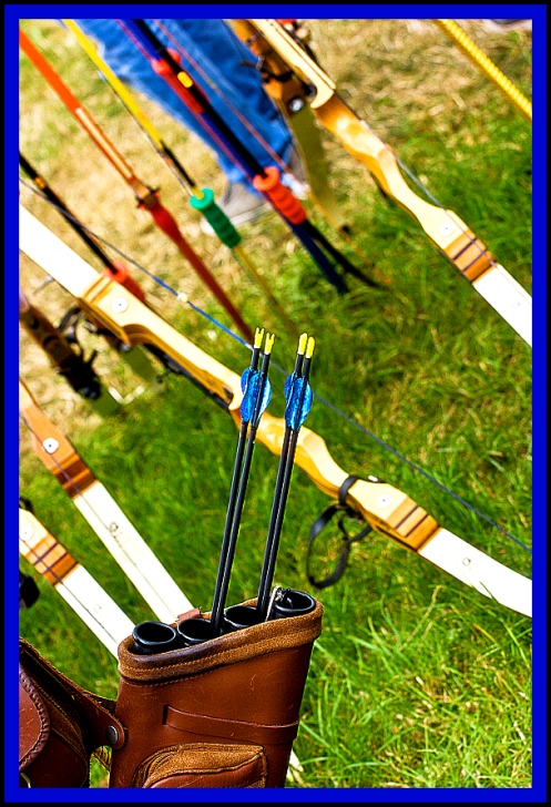 Archery equipment shot at an angle. Bows, arrows, and quiver.
